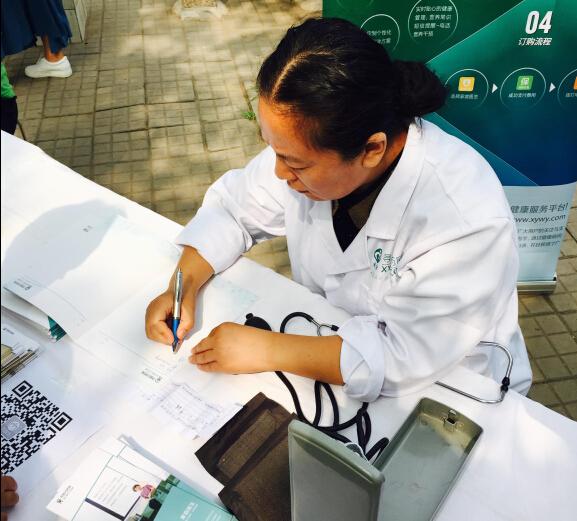 寻医问药网的家庭医生细心的为前来咨询的社区老人们写上建议和一些常规急救措施。