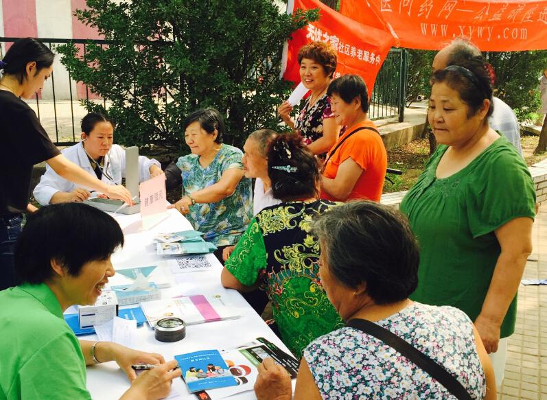 寻医问药网首席医师认真的为居民们测量血压,居民们也从自身健康和医师讨论。