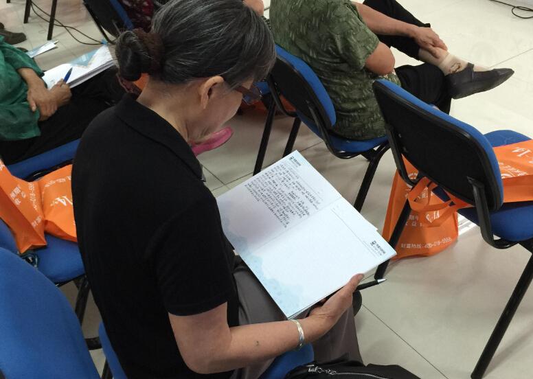 对于家庭医生所说的预防和注意的情况,社区的居民认真的记下笔记。