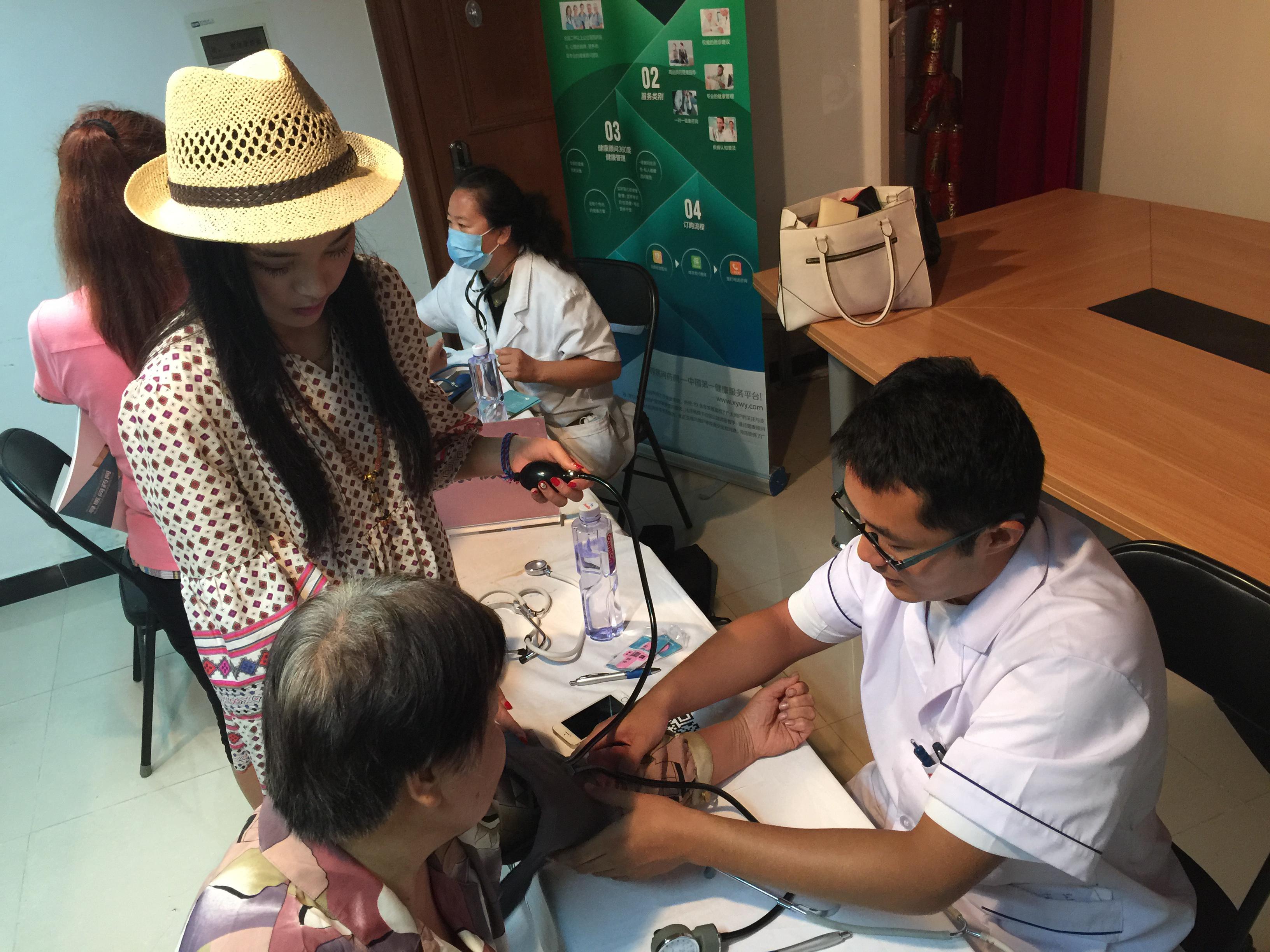 寻医问药网的工作人员辅助着医生为居民测量血压。